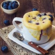 muffin in a mug with berries on table